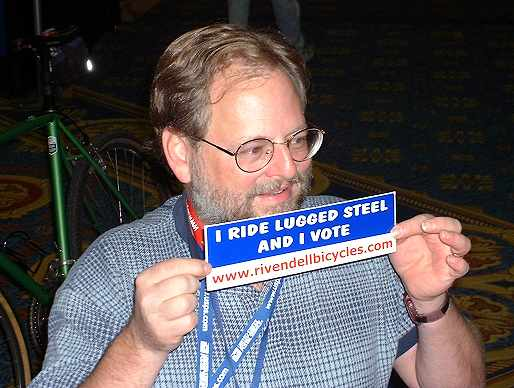 "John Schubert holding bumper sticker reading ""I ride lugged steel and I vote."""